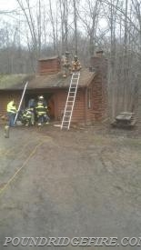 South Salem members operate on the roof of the structure while members from Pound Ridge check for extension inside the structure.